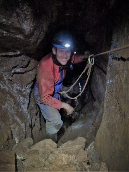Mine explorer traversing a deep mine shaft near St. Ives, Cornwall.