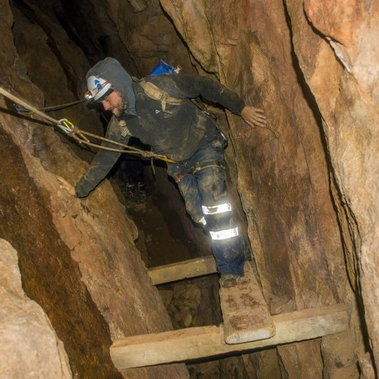 Mine explorer climbing a mineshaft near St. Just, Cornwall
