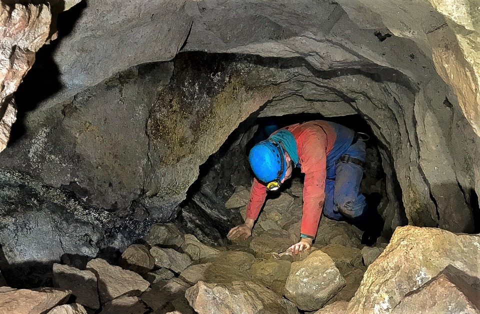 Mine explorer crawling through a tunnel in a Cornish tin mine