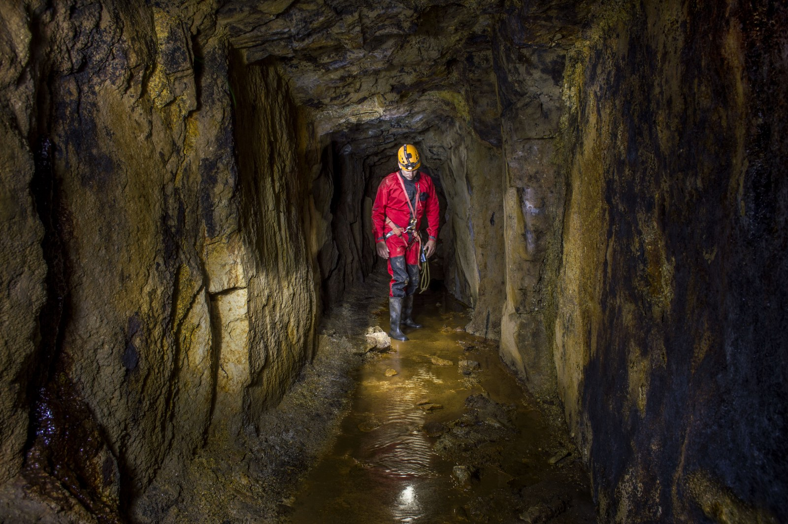 Mine explorer walking along a cross cut in a Cornish tin mine.