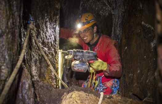 Cornwall Underground Adventure guide bolting a traverse line in a Cornish tin mine