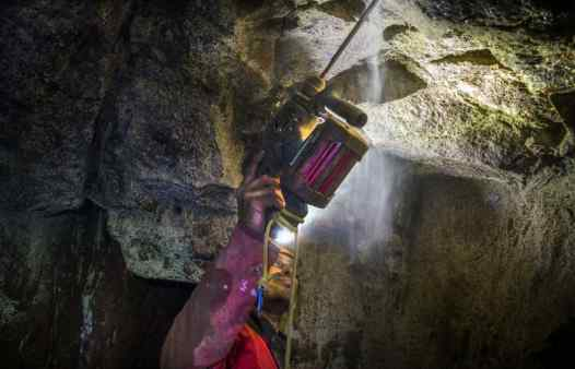 Cornwall Underground Adventures professional mine guide installing a caving bolt in a Cornish tin mine.