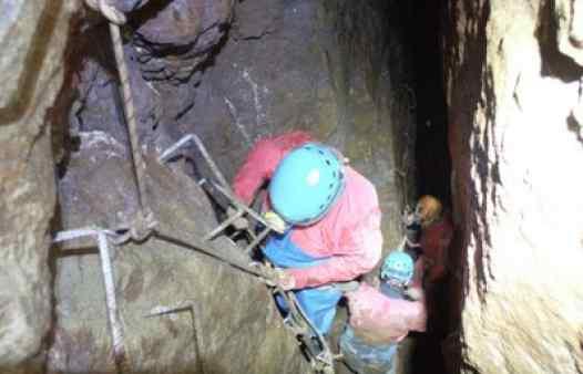 Mine explorer descending a ladder in a Cornish tin mine.
